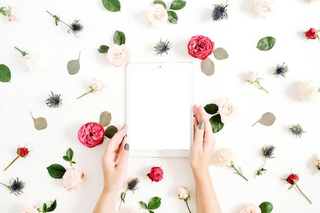 흰색에 빨간색과 베이지 색 장미 꽃 봉 오리와 꽃 프레임에 타블렛으로 여자의 손