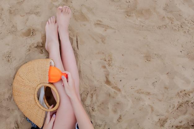 Нога девушки и рука выбирают солнцезащитный крем из соломенного мешка на фоне песка, вид сверху