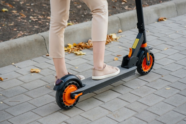 Girl's legs close up on an electric scooter. modern transport vehicle.