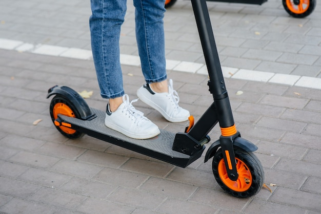 Ноги девушки заделывают на электросамокате. современное транспортное средство.