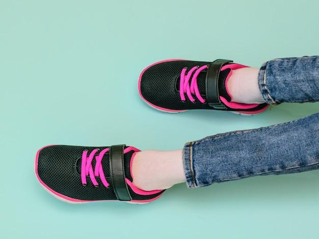 Ноги девочки в рваных джинсах и черно-красных кроссовках