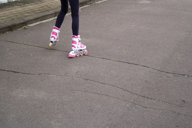 The girl's legs in white and pink rollers on the asphalt, which is cracked. riding on a bad road.