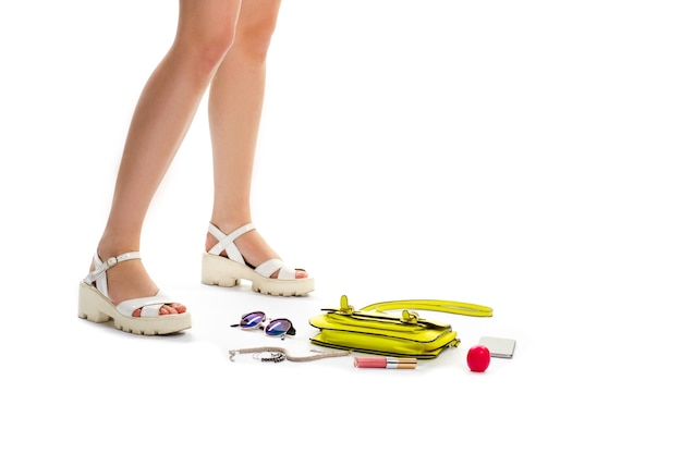 Girl's legs in white sandals. sunglasses near lime bag. don't forget your things. cosmetics and stylish accessories.