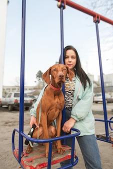 Хозяин девушки обнимает красивую собаку, сидящую на качелях и смотрящую в камеру.