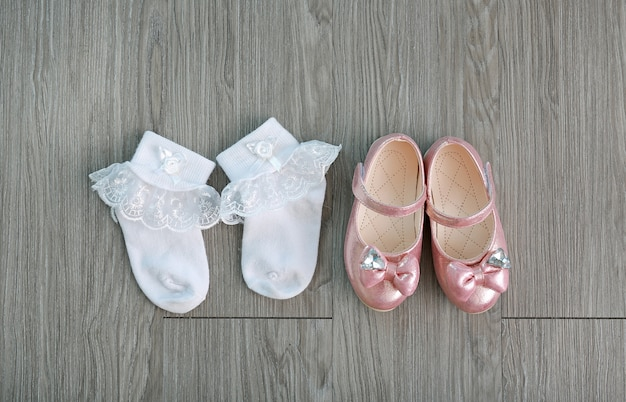 Girl's small shoes with white socks on wood