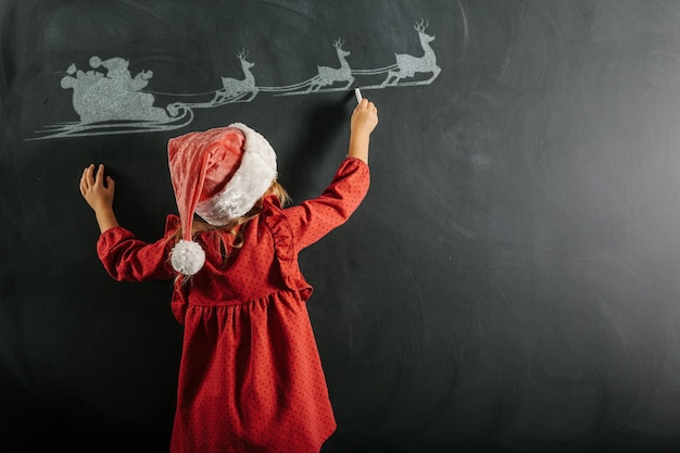 A girl in santa claus hat draws christmas drawing on the blackboard