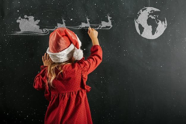 A girl in santa claus hat draws christmas drawing
