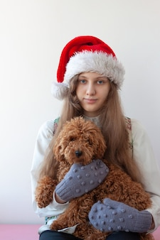 A girl in a santa claus hat holds a poodle in her arms.