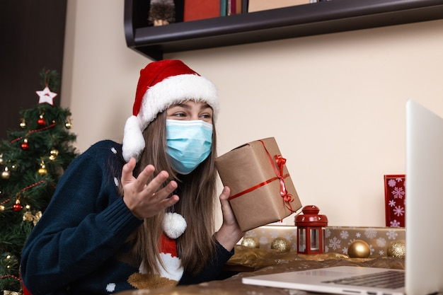 Girl in santa claus hat in medical mask talks gives a gift using laptop for video call friends and parents. the room is festively decorated. christmas during coronavirus.