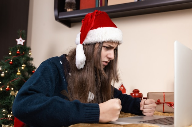 Girl in santa claus hat talks using laptop for video call friends and parents. the room is festively decorated.