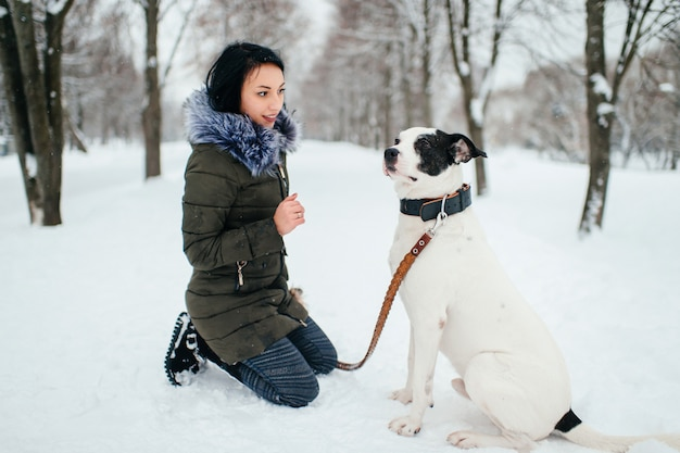 Girl sat down on her knees in snow in front of her dog.
