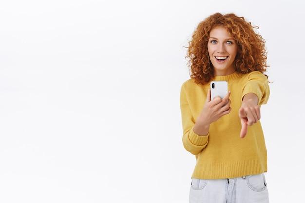 スマホでの写真撮影のポーズに満足した女の子。魅力的な感情的な赤毛の巻き毛の女性は、携帯電話を保持し、人差し指でカメラを指して、嬉しそうに笑って、白い壁
