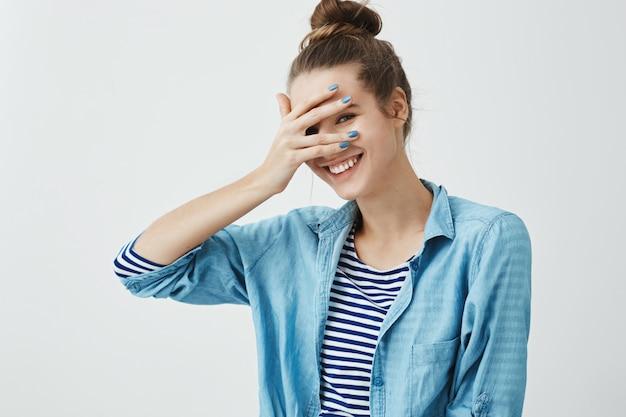 Девушка произносит глупые слова и смущается. внутренний снимок милой стройной женщины в стильной одежде, закрывающей глаза рукой, но выглядывающей, широко улыбающейся, выражающей положительные эмоции