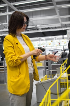 Girl scans a purchase in a store or supermarket Premium Photo