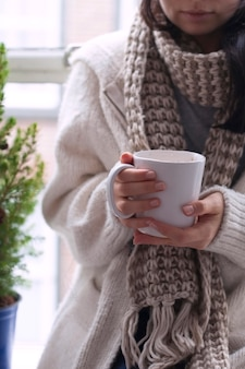Girl in scarf, coffee mug in hands near window christmas tree
