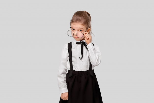 Girl in a school uniform holds round glasses and looks inquiringly
