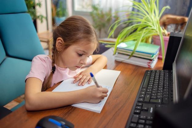 Girl schoolgirl does school homework at home in front of a computer.