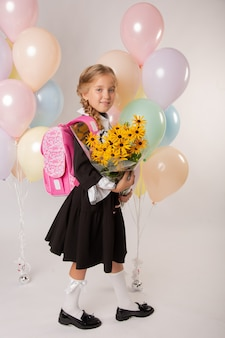 Девушка школьница, первоклассница в школьной форме на белом фоне с шарами и цветами
