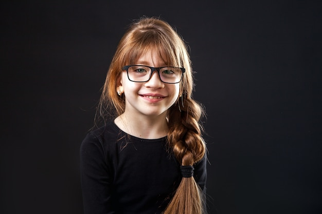 Girl, schoolgirl in glasses with pigtail smiling in the studio on a black background