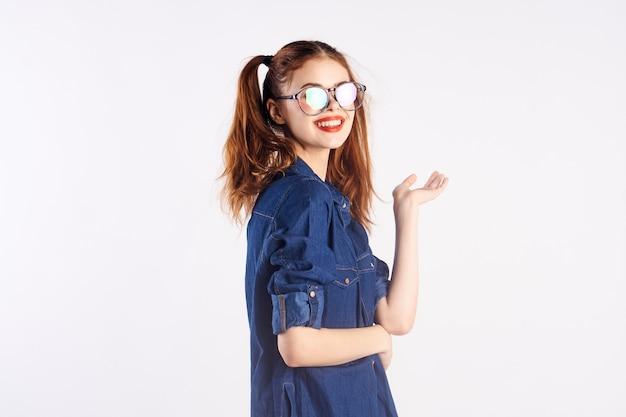 Девушка школьница в студии на белом фоне в очках