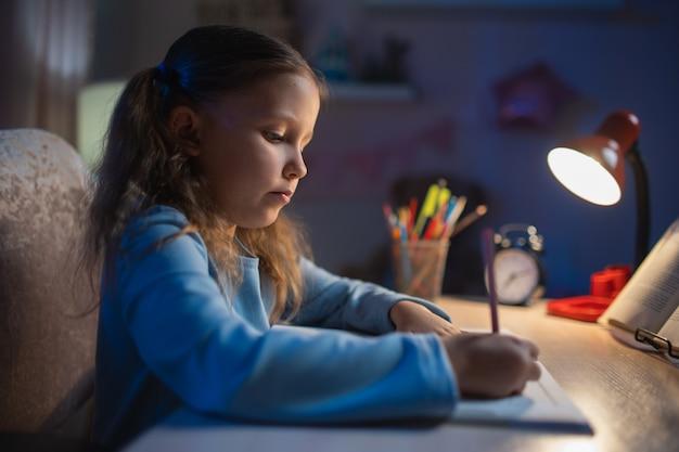 女子校生中学校は学校から家で夕方に宿題をします。本から勉強し、部屋にランプを置いてテーブルに座っている練習帳に書く
