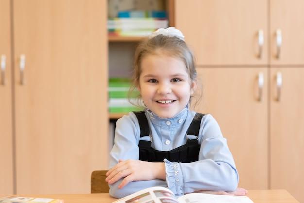 Школьница сидит за партой с книгами и улыбается. для любых целей.