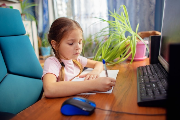 Girl schoolgirl sits at home at a computer desk and writes in a notebook with a pen.