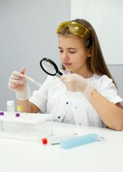 Ученый девушка с увеличительным стеклом и пробиркой