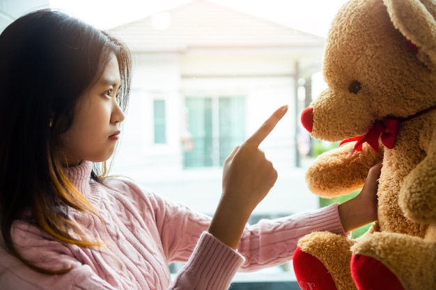 The girl scolding teddy bear in the bedroom of her home