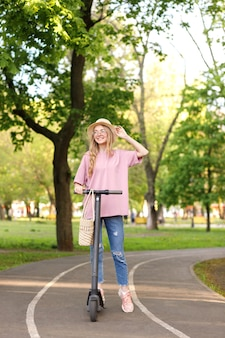Girl on a scooter in the park in the summer on a walk