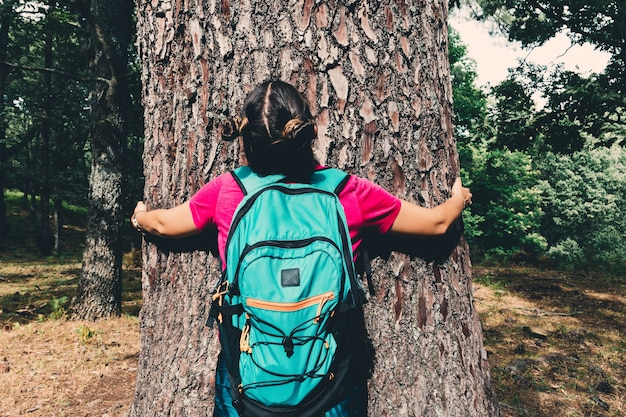 Girl scout with a backpack hugging a tree.