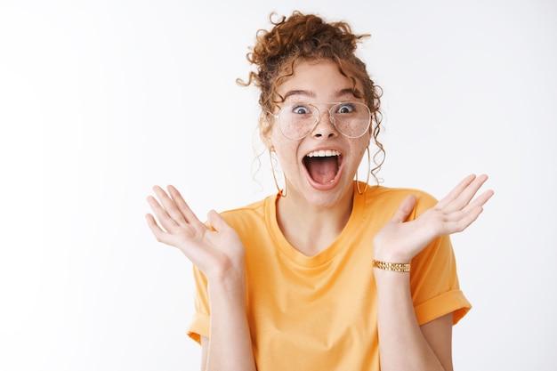 소녀 비명은 굉장한 소식을 듣습니다. 흰색 배경에 서서 예상치 못한 성공을 축하하며 활짝 웃고 있는 여행 투어에서 우승한 깜짝 놀란 빨간 머리 여성