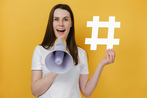 Girl screaming in megaphone showing hashtag sign