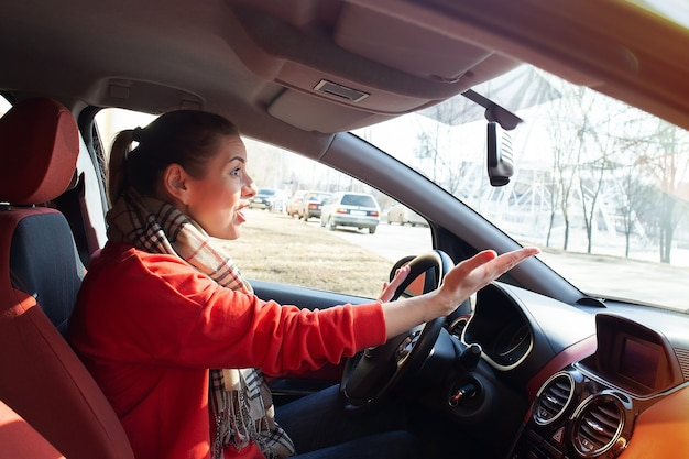 The girl screams behind the wheel of car