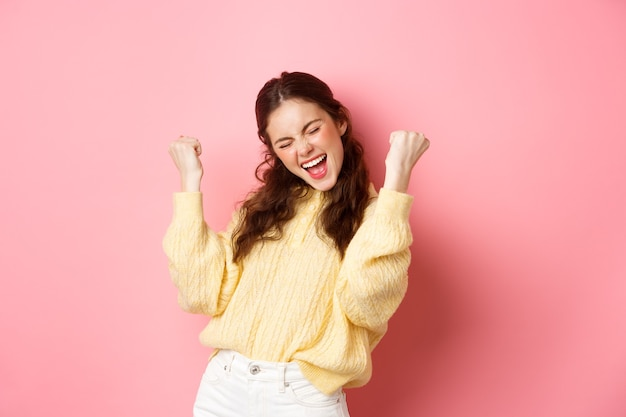 소녀는 기쁨과 주먹 펌프로 비명을 지르며 예라고 말하고 목표 또는 성공을 달성하고 성취를 축하하고 승리하고 승리하며 분홍색 벽 위에 서 있습니다.