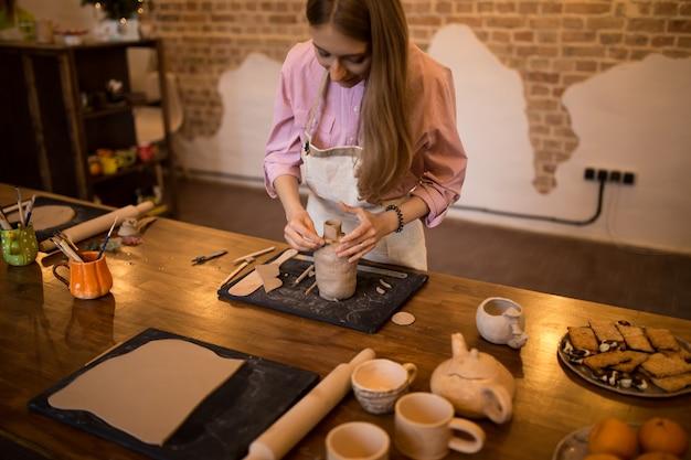 女の子は陶器で粘土の水差しを彫刻します。