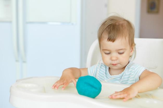 女の子は粘土から彫刻します。子供はハリネズミのクラフトを作ります。つまようじによる細かい運動能力の発達