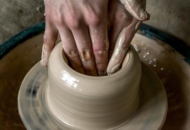 점토 냄비 근접 촬영에서 소녀 조각입니다. 클레이 클로즈업 모델링. 빠르게 움직이는 원에서 하얀 점토로 배를 만드는 백인 남자. 예술, 창의성. 우크라이나, 문화적 전통. 취미