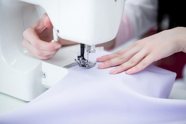 Девушка швея шьет на швейную машинку