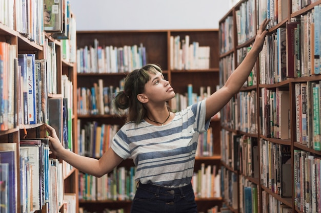 Girl searching bookshelf