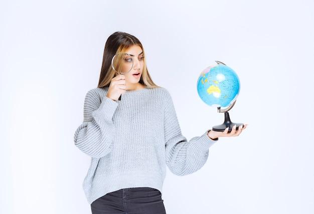 Ragazza alla ricerca di posizioni in tutto il mondo con una lente d'ingrandimento.