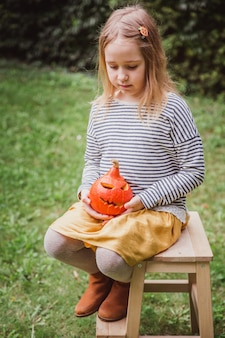Girl seats on wooden chair and holds little pumpkin jack o lanterns