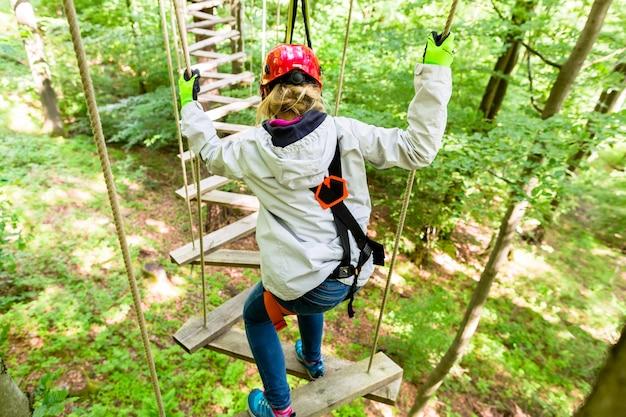Девушка видна сверху, поднимающаяся на веревочный курс