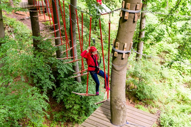 Girl seen from above climbing in high rope course