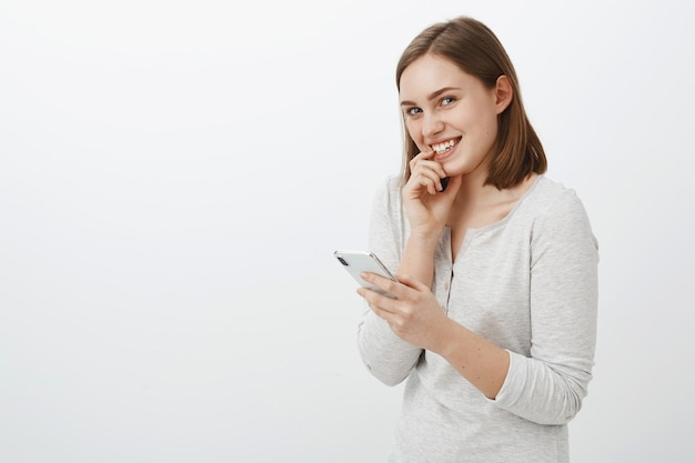 Девушка отправляет рискованное сообщение крутому парню, кокетливо посмеиваясь и глядя, радостно улыбаясь, застенчиво прижимая палец к губе, и смартфон в руке, удивленно и возбужденно стоит над серой стеной
