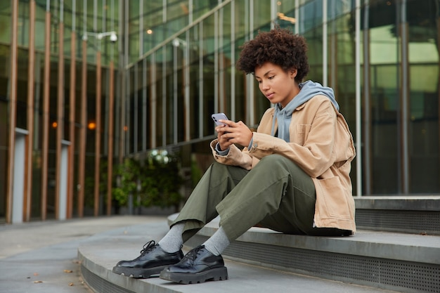Girl sends sms message to friend on smartphone device wears stylish clothes sits on steps near modern glass building searches information