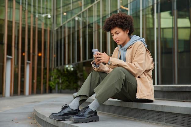 女の子はスマートフォンデバイスで友人にsmsメッセージを送信しますスタイリッシュな服を着ています現代のガラスの建物の近くの階段に座って情報を検索します