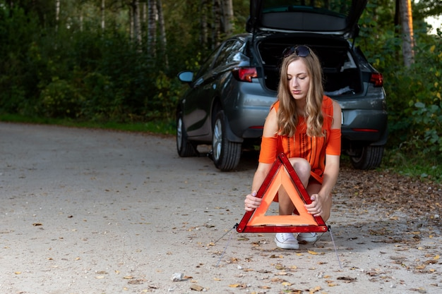 Girl sets a triangle in back of broken car