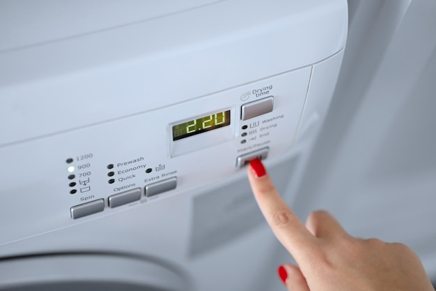 The girl sets the washing program for the washing machine.
