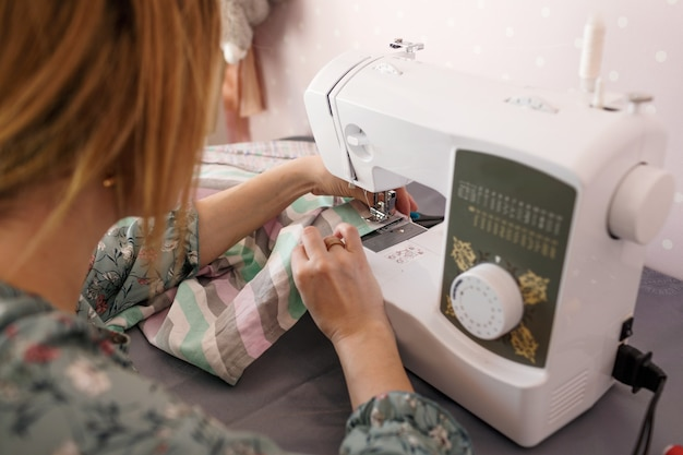 A girl sews on a sewing machine at home.rear view is a favorite hobby. own production of clothing.